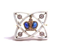 A Imperial Faberge presentation brooch, Enamelled translucent white over a dappled guillochage with brilliant cut diamonds centred by a cabochon sapphire and diamond set Romanov crown, contained in its original silk and velvet lined fitted leather case the lid gilded with an Imperial Eagle. Workmaster: Alfred Thielemann, St. Petersburg, circa 1909,Purchased by the Imperial Cabinet from Faberge on 8th June 1909 for 90 roubles. Then given to the Tsarina Alexandra Feodorovna
