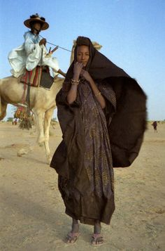 """Young Wodaabe woman in the windy Sahel. In contrast, other Fulbe as well as other ethnic groups sometimes refer to the Wodaabe as """"Bororo"""", a sometimes pejorative name, translated into English as """"Cattle Fulani"""", and meaning """"those who dwell in cattle camps""""."""