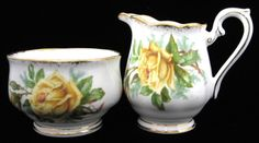 This is an English made Royal Albert, England cream and sugar set made by in the yellow Tea Rose pattern with sponged gold trim. The cream, creamer or milk jug measures 3.5 inches high, the sugar basi