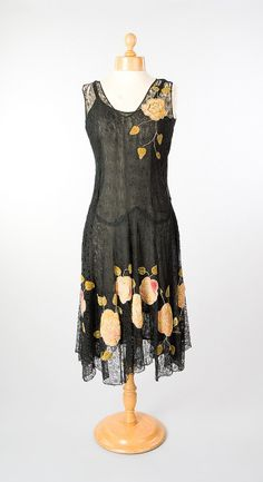 Chiffon evening dress,1920. Skirt decorated with band of appliquéd orange and red velvet flowers sewn with spiralled chain stitch in silver metallic thread and with green velvet leaves.  © Aberdeen Art Gallery & Museums Collections.