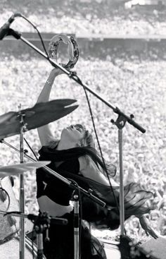 Fleetwood Mac: Stevie Nicks on stage playing tambourine at his drum kit - great photo of the crowd and microphones, as well as ACTION photography in this black and white music history picture. #cSw:) DRUMMER DRUMMING. Pinned via rooze2 MUSIC & MUSICIANS #Pinterest board.