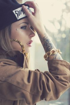 Dimepiece hat, Gold jewellery, black ink and dermal anchor on the face.