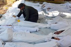 A man holds the body of a dead child among bodies of people activists say were killed by nerve gas in the Ghouta region, in the Duma neighbourhood of Damascus August 21, 2013. (Bassam Khabieh/Reuters)