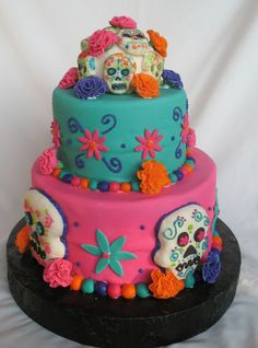 Dia De Los Muertos - Top tier: pumpkin sponge cake with vanilla mousse filling covered in fondant. Bottom tier: sponge cake with apricot mousse filling and coverd in fondant. Fondant skull hand deocorated with edible markers, fondant flowers, rice crispy treat skulls coverd in fondant, fondant flowers and fondant balls trim the cake.
