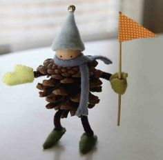 D I Y ....Pine cone boy wearing a hat, gloves, scarf and wearing shoes and  holding a flag