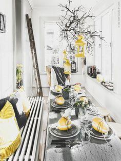 Duka upp till påsklunch på verandan. Ljuslyktan ROTERA i en gren ovanför bordet. Kuddfodralen GULLKLOCKA och GURLI matchar dagens färgtema.