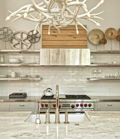 kitchens - gray modern kitchen cabinets stainless steel countertops sink in kitchen island marble countertops subway tiles backsplash stainless steel floating shelves white faux antlers chandelier