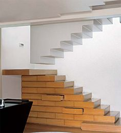 Revestida de pau-marfim, a parte inferior da escada (com 2,75 x 1,44 x 0,75 m) apoia-se numa estrutura de madeira. Dentro dela, foram embutidas 13 gavetas. Um patamar (com 1,60 x 0,18 x 0,75 m) leva ao segundo lance, de estrutura metálica. Para sustentar esse bloco, instalou-se uma viga no teto. Projeto de Romildo Silva Filho.