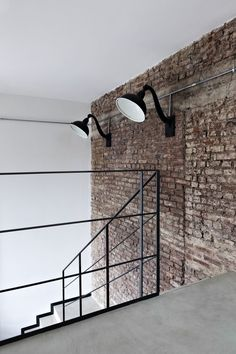 Minimal lighting and hand rail, plus stark white walls, along side concrete floor & exposed brick walls