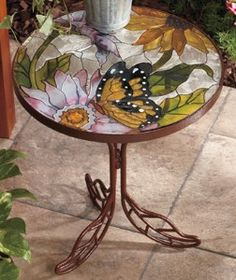 Stained Glass Accent Table looks beautiful holding a potted plant or as a decorative piece on your patio. These lovely tables have garden-themed, stained glass tops on decorative metal bases. Each features pink and yellow flowers with leaves and stems in Mosaic Crafts, Mosaic Art, Mosaic Glass, Mosaic Tiles, Fused Glass, Mosaics, Stained Glass Projects, Stained Glass Patterns, Stained Glass Art