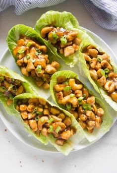 Six lettuce leaves filled with cashews, chicken, and a homemade sauce, all on a white plate.