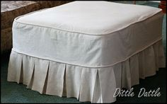 How to make an ottoman slip cover using a drop cloth, wish I could make something like this to put over box spring because it is such a challenge to make those bedskirts stay in place when you put the mattress back on