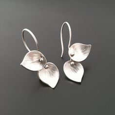 """These earrings are a sweet compliment to the Lotus, Double Leaf, Bamboo, or Trillium pendants.  Each leaf is hammer textured and dapped into a concave form.  The top leaf is stationary while the bottom dangles for added movement and interest.  Sterling silver, 1"""" long by 3/4"""" wide.  These are a great """"everyday"""" pair of earrings."""