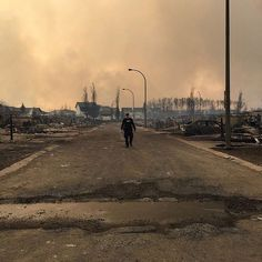 A police officer walks past burnt-out houses in #FortMcMurray Canada. The Canadian province of Alberta has declared a state of emergency after a raging wildfire engulfed several neighbourhoods and forced the evacuation of the entire city. More than 80000 residents were ordered to leave after shifting winds saw the blaze go from being largely controlled to a nasty ugly inferno as described by the local fire chief.  Photo: RCMP/AFP/Getty Images by guardian via Instagram w/ifttt