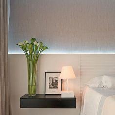 Cabeceira em painéis de madeira cancelada no espaço da cama e lisa nos criados…