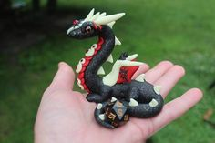 """""""Black Glitter, red and glow in the dark!  What more could you ask for! Swarovski crystals on his neck, head, and wings, with a D20 dice in his tail. Perfect for the active gamer. (die is removable)  Handcrafted with Love from high quality  polymer clay. My Dragons average 3 1/2"""" to 4"""" tall and larger. Will be 40"""""""