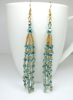 Made using aqua apollo czech glass firepolish beads and galvanised gold seed beads, all woven together with strong fireline thread and finished with gold plated fish hook ear wires. There are 5 strands to each tasseled earring.   The length of the earrings without the earwires are 9.2 cm (3.6 inch)