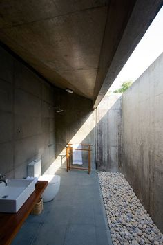 Monolithic concrete boxes containing the various rooms rest on the uneven ground and cantilever over the water, while trees grow in the gaps between.