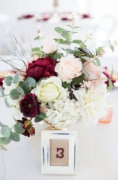 Burgundy wedding flowers and a pop of shades of pink for a beautiful wedding table centerpiece | Photo by Annabeth Kierspe