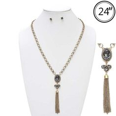 Gold link chain necklace with an ornate vintage crystal oval and tassel