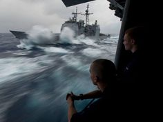 Hull Technician Fireman Douglas Anderson, left, and Hull Technician Fireman Patrick Zembol watch the Ticonderoga-class guided-missile cruiser USS Bunker Hill take on fuel in heavy seas during a refueling at sea with the Nimitz-class aircraft carrier USS Carl Vinson.