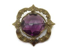 A lovely vintage amethyst purple Czech glass brooch in a fancy brass setting featuring flowers and ivy leaves.  Measures about 1.75 across. No