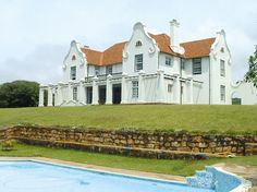 Cape Dutch style home. #Botha-House, South Africa.  Stucco gable ends and wrapped trellis detail.