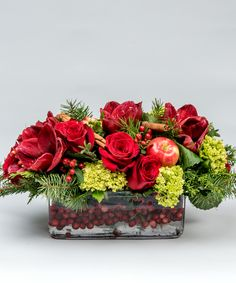 Joyous Centerpiece A wonderful collection of red roses and amaryllis accented with winter greens, berries, and seasonal textures designed in a cranberry filled rectangular glass vase creates this stunning and festive arrangement.