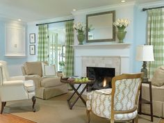 This living room boasts a quaint yet sophisticated style, featuring green plaid curtains, a stone fireplace and a mix of neutral armchairs. Green vases on the mantle display flowers and complement the drapery. One patterned chair adds interest and texture to the space.