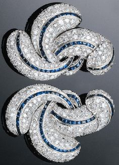 A PAIR OF ART DECO PLATINUM, GOLD, DIAMOND AND SAPPHIRE CLIPS, 1930S. Designed as swirls of pavé diamonds with a line of sapphires running through each swirl. #ArtDeco #clip