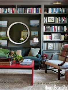 Look at the wonderful effect of this dark bookcase wall, with the indention for a sofa! Notice how the red coffee table pops red in the books, in accent pillows and on the plaid throw (over the occasional chair back.) Love the art in combination with the big round mirror!