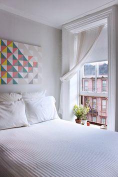 明るく開放的なワンルーム的な部屋のベッドサイドの可愛らしい上げ下げ窓