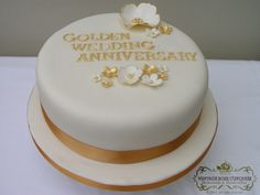 Golden wedding anniversary cake with gold and cream flowers.