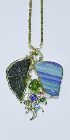Boulder opal pendant with moldavite, peridot, tanzanite, topaz and ruby in 22k and 18k gold.  Opals from Bill Kasso