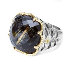 With a plush cushion-cut shape, Rutilated Quartz is given depth and dimension over velvety Black Onyx. Rich 18k yellow gold displays the primally provocative charred colour, and crescent-woven sterling silver design elements demand attention from every angle. 603-749-3129