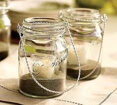Hanging Mason Jar - Bring found-object chic to outdoor dining. Inspired by Mason jars used to preserve homemade jams, our candle holders are made of thick-plated glass with wire handles. Use them for casual candlelit ambiance. Mason Jar Lanterns, Hanging Mason Jars, Candle Jars, Hanging Candles, Diy Hanging, Candle Lanterns, Hanging Lights, String Lights, White Lanterns