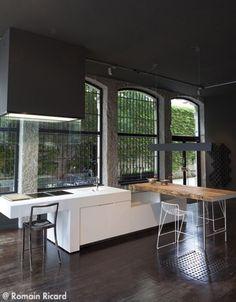 reforma cocina en loft rehabilitado, isla para fregadero y zona de cocción como mesa de madera sobre soportes metálicos, suelo de parquet.