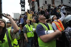Construction workers watch as the beam is hoisted.