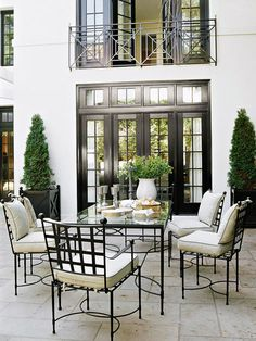Sophisticated patio dining area. Natural stone and cream fabrics look rich with the glossy black details. Delicate lines on the table and chairs are reflected in the home's windows and balcony railing. Via TraditionalHome.com