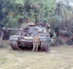 """ Driver of tank C-35 standing with a South Vietnamese armor officer during operations near Phu My, 1968. A lucky horseshoe hangs from the 90mm gun tube; sandbags on the front slope provide..."