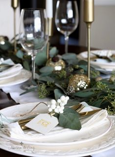 Casual Chic Green and White Christmas Tablescape green and white christmas tablescape wine glasses brass candlesticks gold ornaments white dinnerware