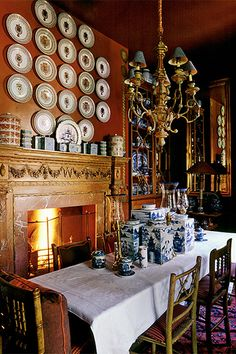 In the breakfast room of Cole Park, interior designer Anouska Hempel's English country residence, porcelain collections are displayed on the wall, mantle and dining table.