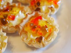 This mini savory cheesecake recipe uses phyllo cups as the crust and a delicious Neufchâtel filling. Topped with sweet and spicy pepper jelly for a kick!
