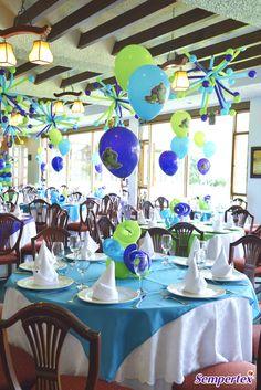 Los globos nos permiten crear fácilmente centros de mesa atractivos. En esta fiesta podemos apreciar uno elaborado con un cuarteto de globos R-6, 3 tubitos 260 Fashion Azul Caribe, Verde Lima y Violeta en forma de espiral y tres globos Policromía Monsters Inc inflados con helio.