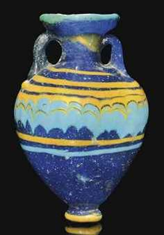 A GREEK CORE-FORMED GLASS AMPHORISKOS CIRCA 6TH-5TH CENTURY B.C. The dark blue ovoid body with cylindrical neck and everted rim, applied opaque yellow and turquoise marvered threads wound spirally and tooled into a festoon pattern, yellow and turquoise bands below, applied yellow trail around foot, turquoise trail around rim, twin applied handles 3 1/8 in. (8 cm.) high