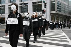 This picture shows a group of individuals protesting against war. all of them covering their faces with masks and wearing signs that read multiple religious statements.