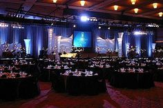 Black table setting and stage with white uplit draping behind the stage.