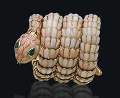 A Rare Coral and Emerald Snake Watch-Bracelet, by Bulgari - Designed as a coiled snake, the sprung body composed of coral scales, the head with pear-shaped emerald eyes and hinged jaw opening to reveal the circular dial with polished hour markers and hands, Arabic numerals at 3, 6, 9 and 12 o'clock, in a diamond line bezel, mechanical movement, mounted in gold, 1960s, in burgundy leather fitted Bulgari case Signed Bulgari, dial signed Jaeger-LeCoultre, no. 149837 - Estimate: $187,893…