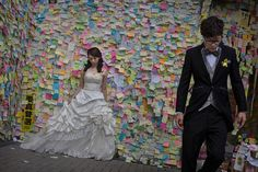 Umbrella Revolution Hong Kong, A Hong Kong couple, who did not give their names, stand near a wall with messages left by protesters as the pose for a wedding photographer prior to their marriage s at the Admiralty ppro-democracy protest site on November 14, 2014 in Hong Kong, Hong Kong. Hong Kong's high court has authorized police to arrest protesters who obstruct bailiffs on the three interim restraining orders. (Photo by Kevin Frayer/Getty Images)