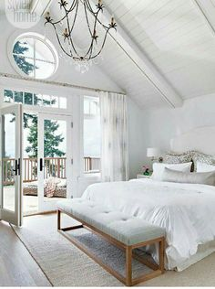 white bedroom with bench at the end of bed